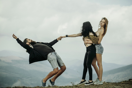 Two pretty girls slim models with naked chest pull bearded man hipster on mountain top on cloudy sky Standard-Bild