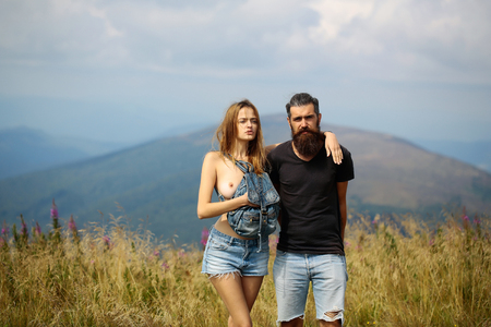 Romantic couple of pretty naked girl with bare chest and handsome bearded man in love embrace on cliff on summer day over mountain tops and sky