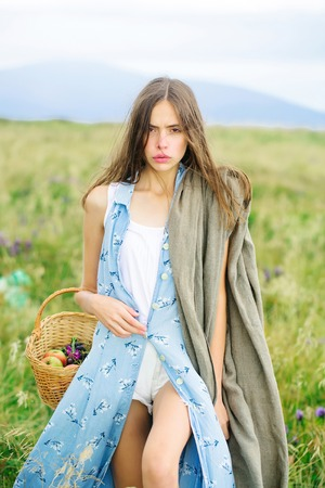 the stands: Pretty cute sexy brunette woman or girl in blue dress stands straight outdoor on beautiful landscape in field with basket Stock Photo