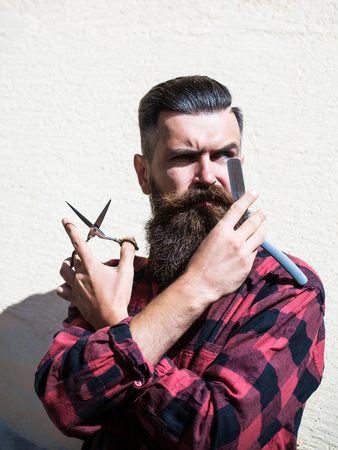 Young man hipster sexy brutal hairdresser with fashion long beard and moustache on handsome thoughtful face holding cut razor and scissors equipment in hand on light wall background Imagens