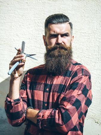Jonge man hipster sexy brutale kapper met mode lange baard en snor op knappe doordachte gelaatsuitdrukking gesneden scheermes en schaar apparatuur in de hand op lichte muur achtergrond