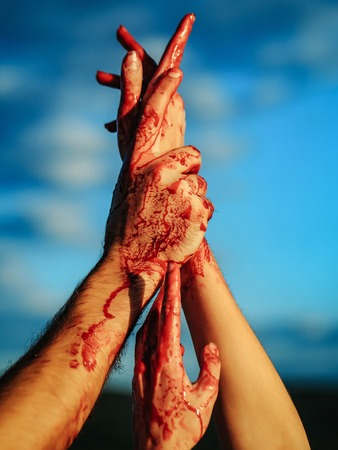 warfare: zombie hands male and female of man war soldier and girl woman with bloody wounds and red blood on skin on blue sky background