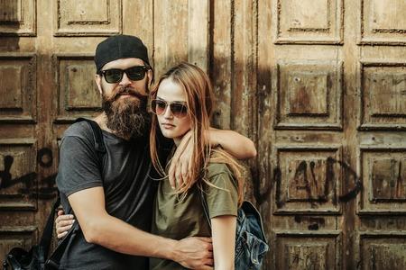 年輕人的時髦與太陽鏡英俊的臉上的鬍鬚和棒球帽在木門背景休閒服擁抱漂亮的女孩 版權商用圖片 - 65086249