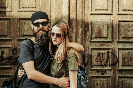 Young man hipster with beard on handsome face in sunglasses and baseball cap hugging pretty girl in casual clothes on wooden door background