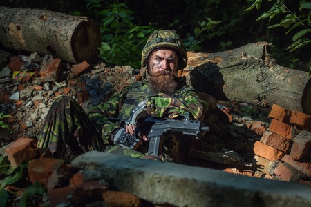 aggressiveness: Young soldier with sad bearded face in military helmet and camouflage with gun on ruined bricks background in forest