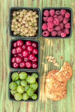 raspberry cherry gooseberry and white grape or currant berry fruit assortment red and green color and peanut cookies with healthy vitamins on wooden or wood table