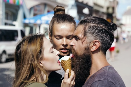 cornet: Young man hipster with bearded handsome face and two pretty girls eating tasty ice creame cornet together on city street background outdoor closeup