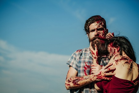Bearded man zombie bloody hipster and creepy girl young woman with wounds and red blood outdoors on blue sky Stock Photo