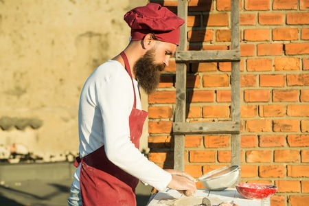 nudelholz: Chef man hipster with long beard on handsome face in red hat and apron white uniform rolling dough with wooden pin on brick wall and ladder background outdoor Lizenzfreie Bilder