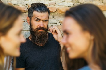Young man hipster brunette with long beard on expressive handsome face in black shirt holding his moustache on background of stone wall and two girls female faces