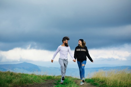 hoody: Couple of handsome bearded man in white shirt and pretty young cute girl or woman in black hoody holding hands and bouncing on cloudy sky background Stock Photo