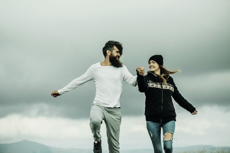 hoody: Couple of handsome bearded man in white shirt and pretty young cute girl or woman in black hoody holding hands and bouncing on gray sky background