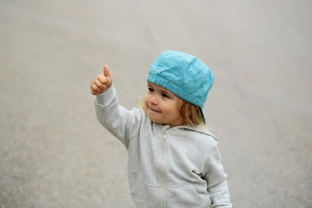 hoody: Cute baby boy child with curly blond curly hair in hoody and blue hat show cool outdoor on gray background
