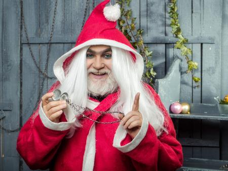 Nieuw jaar man met lachende gezicht met een lange witte baard en haren in het rood Kerstman kerstmis laag houden klok medaillon op ketting