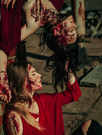 Two zombie girls young women with brunette and blond bloody hair with wounds and red blood for halloween outdoors