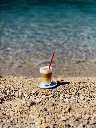 red straw: glass of coffee with red straw on pebble beach on blue sea on sunny summer day