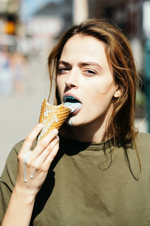 cornet: Young girl with sexy pretty face brown hair in green casual shirt eating tasty blue ice cream cornet on street background outdoor