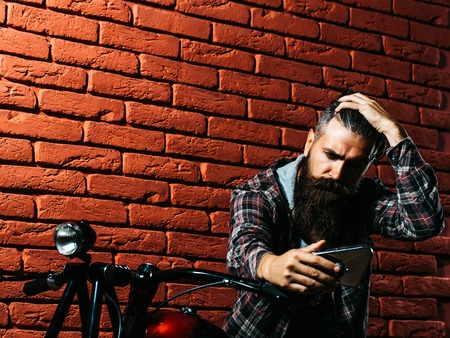 metallized: young handsome bearded man hipster or biker with long beard sitting on metallized motorbike or motor cycle on red brick wall background in garage, copy space Stock Photo