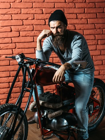 metallized: young handsome bearded man hipster or biker with long beard sitting on metallized motorbike or motor cycle with wheels on red brick wall background in garage
