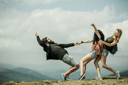Two pretty girls slim models pull bearded man hipster on mountain top on cloudy sky