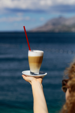 red straw: glass of coffee with red straw on hand on blue sea on sunny summer day