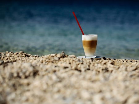 glass of coffee with red straw on pebble beach on blue sea on sunny summer day