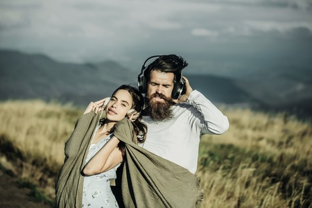 sexi: Young couple of pretty girl covered in blanket and bearded man hipster with beard listen to music with headphones on mountain scene