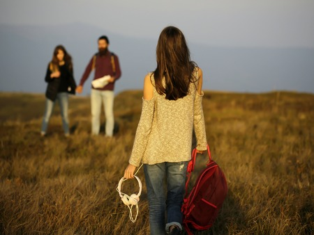 sexi: pretty sexy cute girl or woman with friends holding red backpack with headphones on mountain top on sunny day