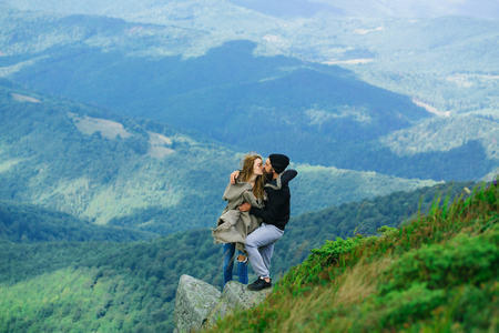 sexi: Romantic couple of pretty girl and handsome man in love embrace on cliff on summer day over mountain tops