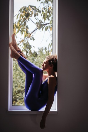 sexi: young pretty cute sexy woman or girl with slim fit body in sporty overall or jumpsuit violet color posing on window with tree on dark background, copy space Stock Photo