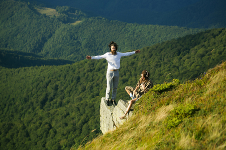 sexi: Romantic couple of pretty woman or girl and handsome bearded man with beard on cliff on summer day over mountain tops with blanket Stock Photo