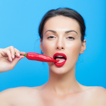 desire: young cute woman or girl portrait with red chilli pepper in sexy lips on pretty face and brunette hair has fashionable makeup on blue background Stock Photo