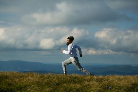 hombres corriendo: Apuesto hombre inconformista con barba y bigote y barba se ejecuta en la parte superior de la montaña en el día soleado de verano en el cielo nublado