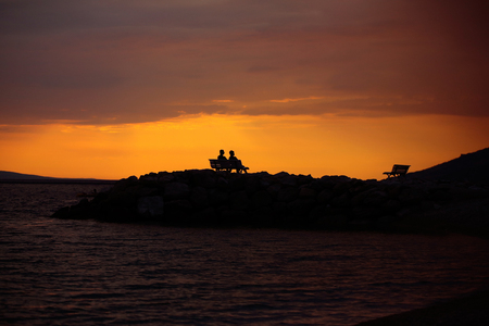 silhouette of people sitting on bench over dark sky with clouds and sea or ocean coast on evening or twilight on natural sunset background Imagens