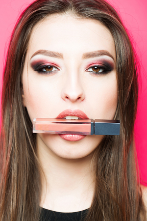 beige lips: Pretty sexy cute woman or girl with long brunette hair and smooth skin has fashion makeup and beige lipstick in mouth or lips on pink background, close up Stock Photo