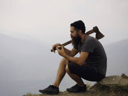 ax man: young handsome bearded hipster man in checkered shirt with long beard holding axe or ax on mountain top on natural background with sky
