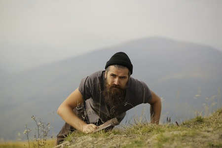 muscularity: lumberjack man hipster with long beard and moustache in gray shirt with axe in hand climbs on mountain top Stock Photo