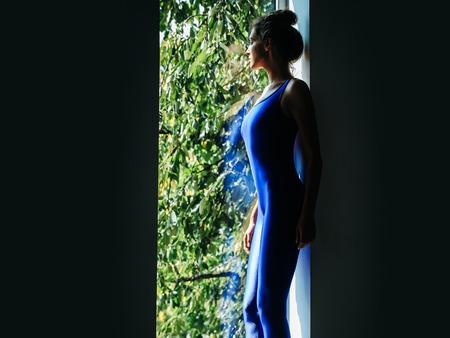 turnanzug: Junge Frau Turner mit prety Gesicht sexy schlanken Körper Silhouette im blauen Trikot stehend in der Nähe Fenster Innen Lizenzfreie Bilder