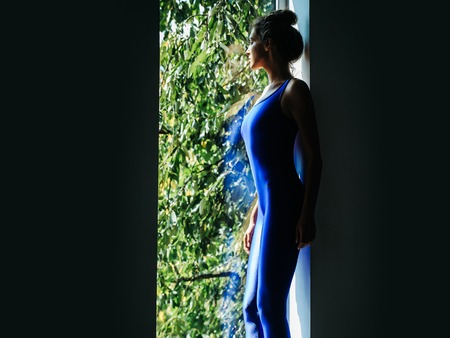 prety: Young woman gymnast with prety face sexy slim body silhouette in blue leotard standing near window indoor