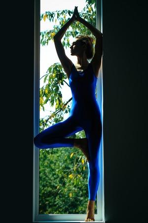 turnanzug: Junge Frau Turner mit prety Gesicht sexy schlanken Körper Silhouette im blauen Trikot in Yoga Asana in der Nähe von Fenster posiert Innen