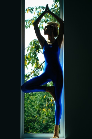 sexi: Young woman gymnast with prety face sexy slim body silhouette in blue leotard posing in yoga asana near window indoor Stock Photo