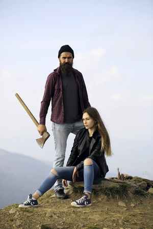 sexi: Couple of handsome bearded hipster in checkered shirt and pretty cute sexy young fashion girl or woman sitting on stone with ax on mountain top on natural background