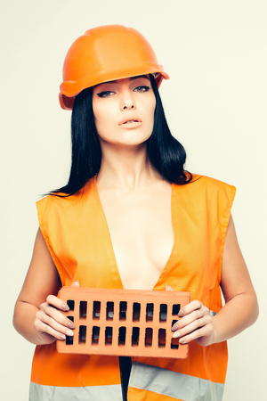 sexi: pretty sexy cute builder woman or mason girl with long straight hair in orange overall uniform holds in hands brick with metal helmet isolated on white background Stock Photo