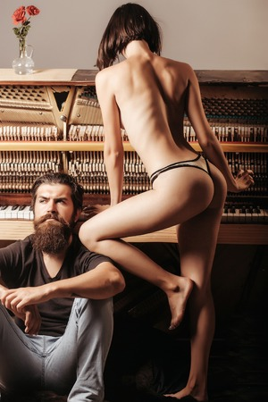 sexi: handsome bearded man with long beard on serious face near young woman or girl with sexy body legs and buttocks has bare back in lingerie near old wooden piano keyboard