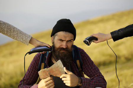 ax man: handsome bearded man with mustache and long lush beard on serious face sit with axe and two female hands try shave him on mountain top on blurred background Stock Photo
