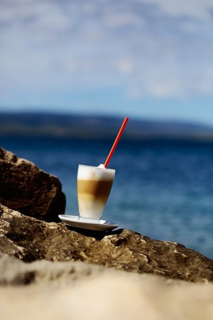 red straw: glass of coffee with red straw on stone on blue sea on sunny summer day Stock Photo