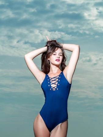 sexi: Young pretty woman or girl with cute sexy face and long brunette hair in blue swimsuit posing with slim fit body outdoor on cloudy sky background