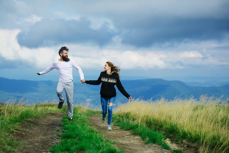 Couple of handsome bearded man in white shirt and pretty young cute girl or woman in black hoody holding hands and bouncing on cloudy sky background Stock Photo