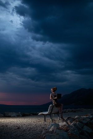 sexi: pretty sexy woman or girl with laptop or computer sits on bench outdoor over dark twilight sky with clouds on beach with sea or ocean water on evening natural background, copy space Stock Photo
