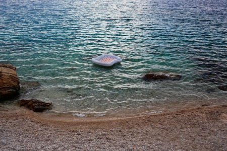 Empty inflatable air bed matrass on blue sea transparent shallow water surface at stony coast on pebble beach Stock Photo